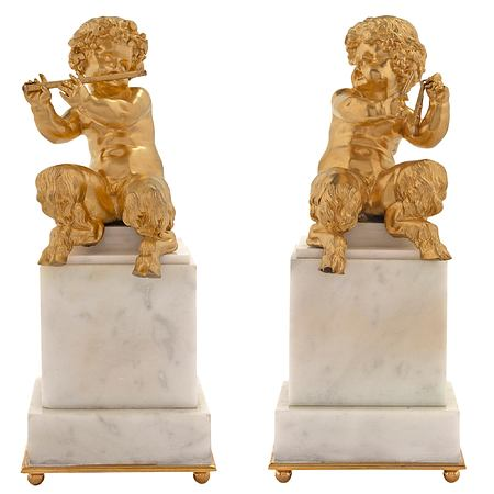 A pair of French mid 19th century Louis XVI st. ormolu and White Carrara marble statues of young cherubs