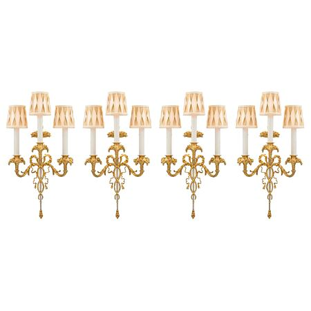 A set of four French 19th century Louis XVI st. ormolu and silvered bronze three arm sconces, by Henry Vian