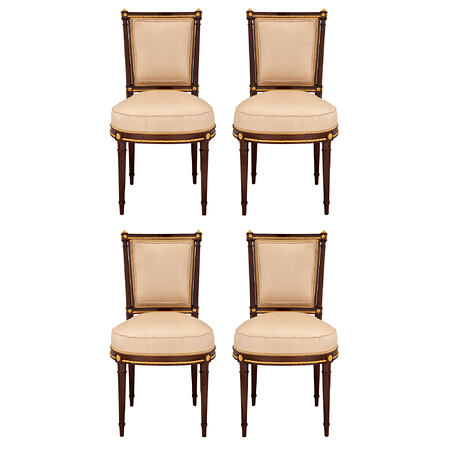 A set of four French 19th century Louis XVI st. mahogany and giltwood side chairs