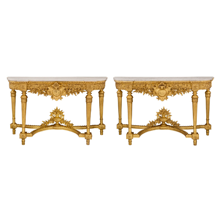 A pair of Italian 19th century Louis XVI st. giltwood and white Carrara marble consoles